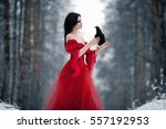 Woman witch in red dress and with raven in her hands in snowy forest. She looks at raven. Around snowing and snowflakes fall on hem of her dress.