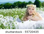 The beautiful bride lies in the field with camomiles with a wreath on a head - stock photo