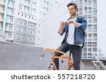 man riding a bicycle outside.... | Shutterstock . vector #557218720