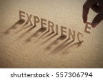 Small photo of EXPERIENCE wood word on compressed or cork board with human's finger at E letter.