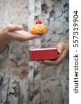 Small photo of Woman holding eclair and red box. Vertical photo