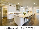 Stock photo white kitchen design features large bar style kitchen island with granite countertop illuminated by 557476213