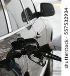 hand holding fuel nozzle to add ... | Shutterstock . vector #557532934