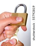 A man opening a golden lock with a key - stock photo