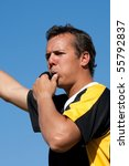 A referee blowing the whistle outdoors - stock photo