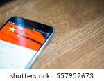 Small photo of Smartphone on wooden background with 5G network sign 25 per cent charge and China flag on the screen.