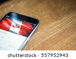 Small photo of Smartphone on wooden background with 5G network sign 25 per cent charge and Canada flag on the screen.