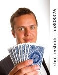 A man holding up a few playing cards - stock photo