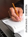 A man writing in his working diary - stock photo