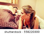 unhappy woman lying in bed... | Shutterstock . vector #558220300