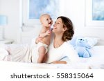 mother and child on a white bed.... | Shutterstock . vector #558315064