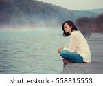 girl  sitting by lake | Shutterstock . vector #558315553
