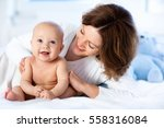mother and child on a white bed.... | Shutterstock . vector #558316084