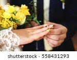 wedding ring on bride's finger | Shutterstock . vector #558431293
