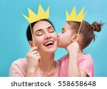 Small photo of Funny family on a background of bright blue wall. Mother and her daughter girl with a paper accessories. Mom and child are holding paper crown on stick.