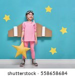 Small photo of Little child girl in an astronaut costume is playing and dreaming of becoming a spaceman. Portrait of funny kid on a background of bright blue wall with yellow stars.