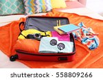 open suitcase with clothes and... | Shutterstock . vector #558809266