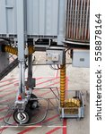 Small photo of Detail of aerobridge rolling wheels and yellow line of air condition supply for airplane.