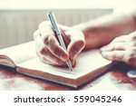 man's hand with a pen writes... | Shutterstock . vector #559045246