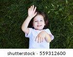 little girl lying on the grass... | Shutterstock . vector #559312600