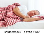 calm mature man sleeps in bed | Shutterstock . vector #559554430