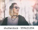 Small photo of perfect winter outfit. stylish fashion blogger wearing a faux fur black coat, accessorized with sunglasses. trendy young woman posing outside on a sunny winter day. vintage grade with a flare.