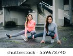 Small photo of Two sporty women stretching long adductor for warming up before urban fitness workout or running training. Latin and caucasian female athletes doing leg stretch exercise outside on rainy winter day.