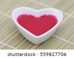 Small photo of Elixir of love, Red philter in heart bowl on bamboo mat background
