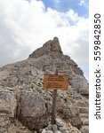 """Small photo of Via ferrata Alpinisteig sign with german and italian text """"Fixed war trail of the Alpini 1915 - 1918 in the direction Col Zwolfer"""" in Sexten Dolomites mountains in South Tyrol, Italy"""
