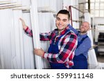 smiling workmen choosing pvc... | Shutterstock . vector #559911148