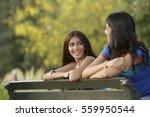 two teen girls on park bench | Shutterstock . vector #559950544