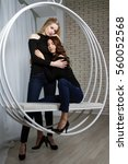 two girls in jeans sitting on a ... | Shutterstock . vector #560052568