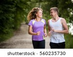 happy couple runners jogging... | Shutterstock . vector #560235730