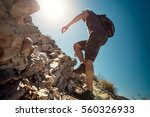 hiker crossing rocky terrain | Shutterstock . vector #560326933