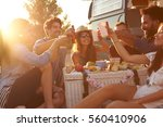 Friends making a toast at a picnic beside their camper van - stock photo
