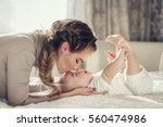 young mother holding her... | Shutterstock . vector #560474986