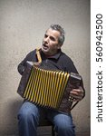 Small photo of old man playing accordion in the street