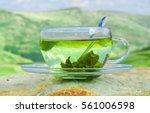 Stock photo green tea time green tea leaves at the bottom of the cup hot tea green tea on a background of 561006598