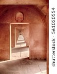 Small photo of A long passageway of red sandstone arches alternate light and shadow details near the entrance to the Taj Mahal in Agra, India