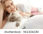 Stock photo beautiful young woman with cute cat lying on bed at home 561326230