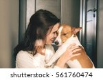 Stock photo young beautiful smiling woman hugging her pet dog at home close up portrait 561760474