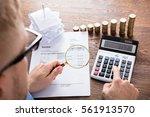Small photo of High Angle View Of A Auditor Hand Calculating Invoice Using Calculator On Desk. Tax Scrutiny And Fraud Investigation Concept
