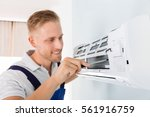 happy male technician repairing ... | Shutterstock . vector #561916759