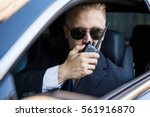Surveillance Man Sitting Inside Car Talking On Walkie Talkie - stock photo