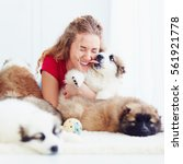 Stock photo funny moment of cute puppy licking laughing girl 561921778