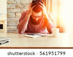 stressed man writing with pen... | Shutterstock . vector #561951799