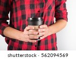 Young female in tartan shirt holding disposable coffee cup in her hands - stock photo