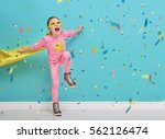 Small photo of Little child plays superhero. Kid on the background of bright blue wall. Girl is throwing confetti and jumping. Yellow, pink and turquoise colors.