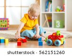 a kid boy playing toy blocks... | Shutterstock . vector #562151260