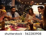 friends eat and talk at a... | Shutterstock . vector #562283908